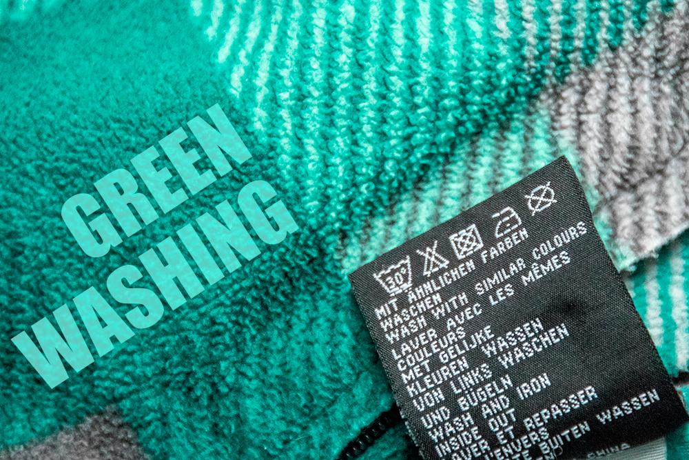 """Nahaufnahme eines Kleidungsstückes und dem Waschetikett, auf dem """"Greenwashing"""" geschrieben steht."""