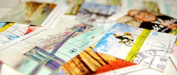 Bild von verschiedenen gestempelten Briefmarken auf einem Schreibtisch