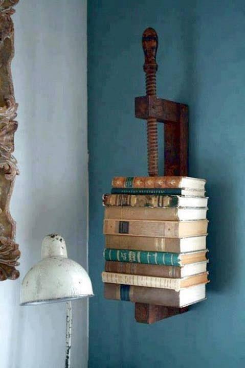 Bücher in einer Schraubzwinge (als Buchregal an der Wand)