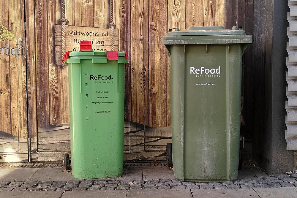 Zwei grüne Lebensmittelmülltonnen von ReFood an einer Straßenecke.