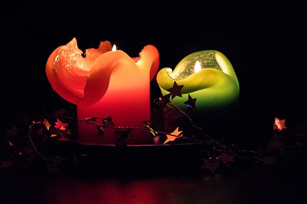 Rote und grüne Kerze brennen im dunkeln