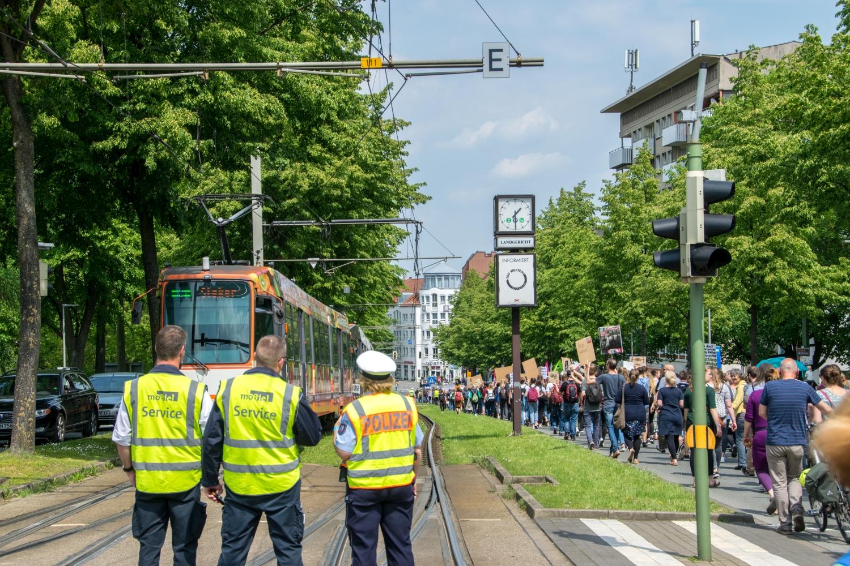Foto: Fridays For Future - Demo in Bielefeld. Im Vordergrund stehen 3 Menschen in Warnwesten (2 von moBiel und 1 Polizistin), links noch eine stehende Straßenbahn und rechts der lange Demonstrationszug auf dem Niederwall Richtung Rathaus.