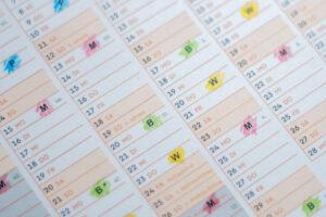 Nahaufnahme eines Abfallkalenders aus Papier mit farbig markierten Tonnen.