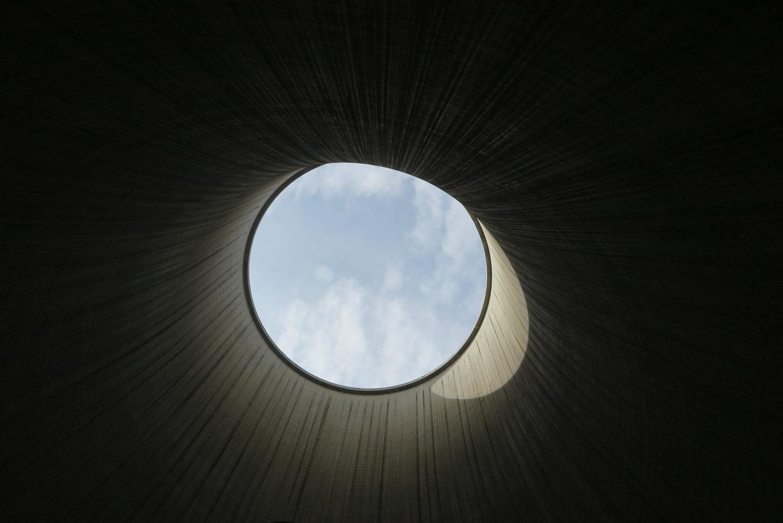 Blick aus dem Inneren eines Kohlekraft-Kühlturms durch die große Öffnung nach oben in den wolkigen Himmel.
