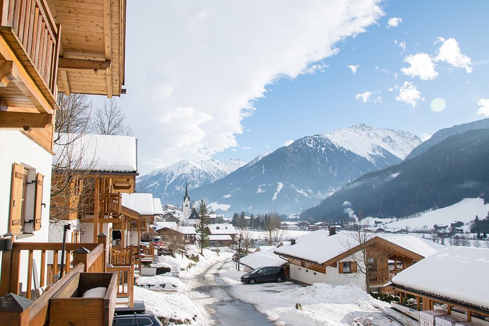 Ein typisch österreichisches Winterdorf. Komfortable, schneebedeckte Holzhäuser vor einer wunderschönen Berg-Kulisse.