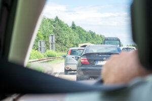 Aus dem Inneren eines Autos kann man über die Schulter des Fahrers einen langen Stau auf der Autobahn erkennen.