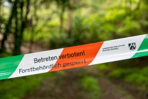 """Ein grün-weiß-rotes Absperrband mit der Aufschrift: """"Betreten verboten! Forstbehördlich gesperrt - Landesbetrieb Wald und Holz Nordrhein-Westfalen"""""""
