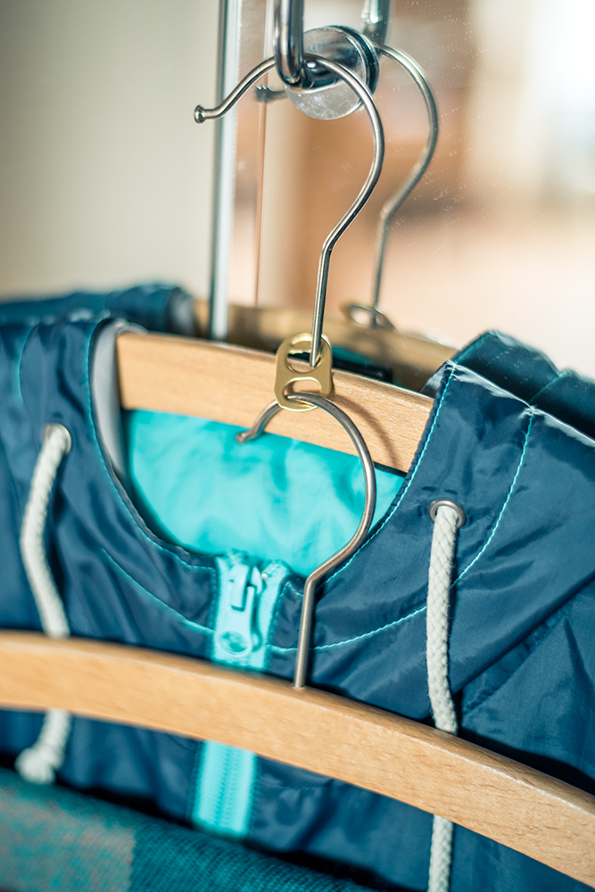 Indem man einen Dosenclip an einem Kleiderbügel befestigt, kann man einen weiteren Kleiderbügel einhängen und Platz sparen.