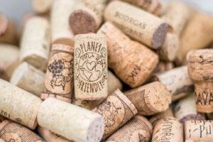 """Viele verschiedene Wein- und Sektkorken auf einem Haufen. Ganz obenauf ein Korken mit der Aufschrift: """"Planet Friendly""""."""
