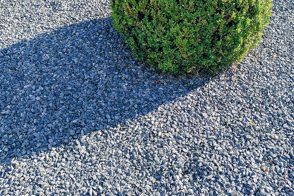Nahaufnahme eines leblosen Steingartens mit einem unecht aussehenden, kreisrunden Busch. Ein toter Garten des Grauens.