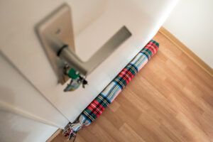 Zugluftstopper vor einer Tür liegend. Schräg von oben fotografiert, mit Türklinke im Bild.